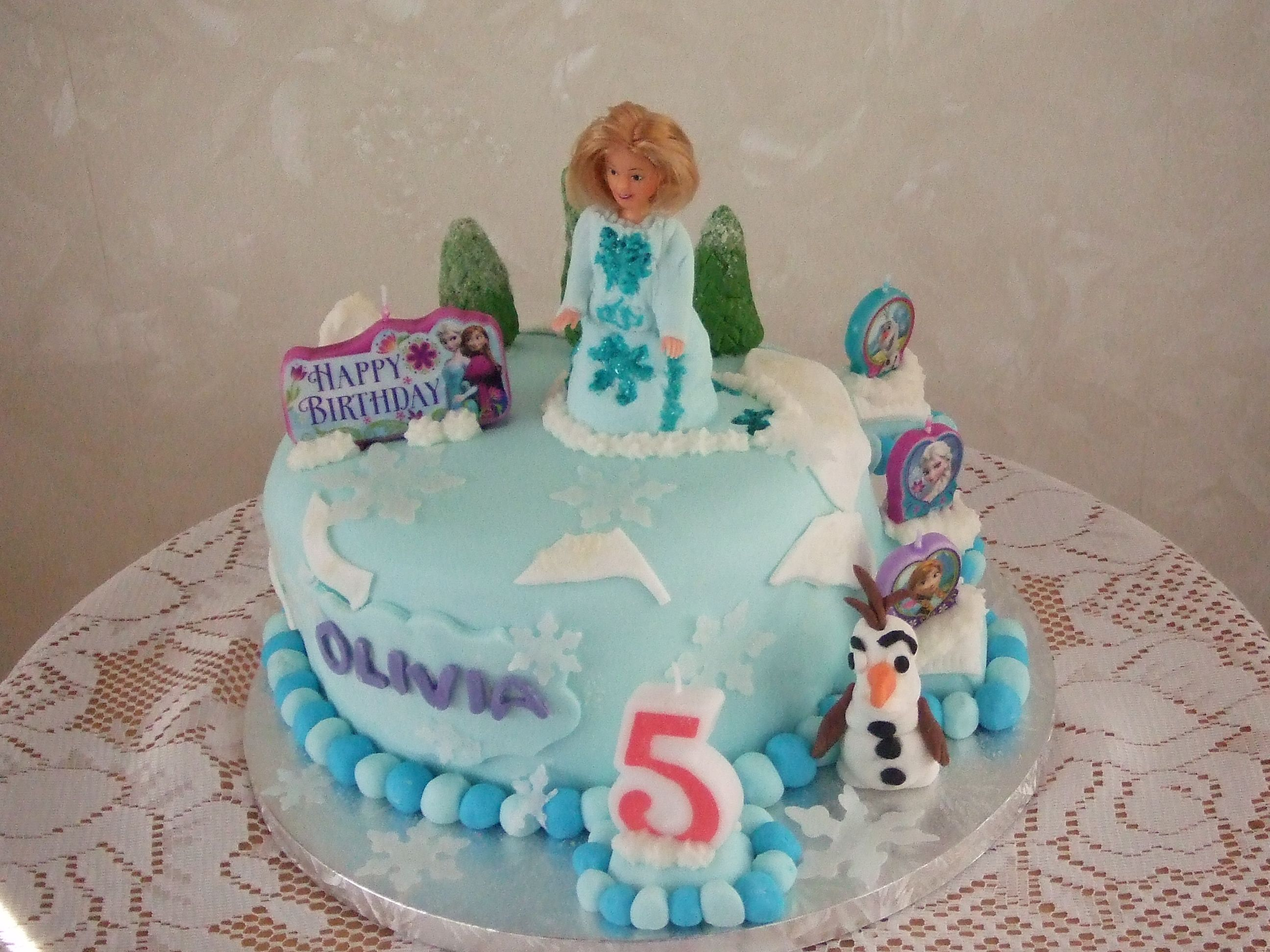 This frozen cake for Olivia's 5th birthday  with handmade  Elsa   and trees steps etc  and with the frozen candles.