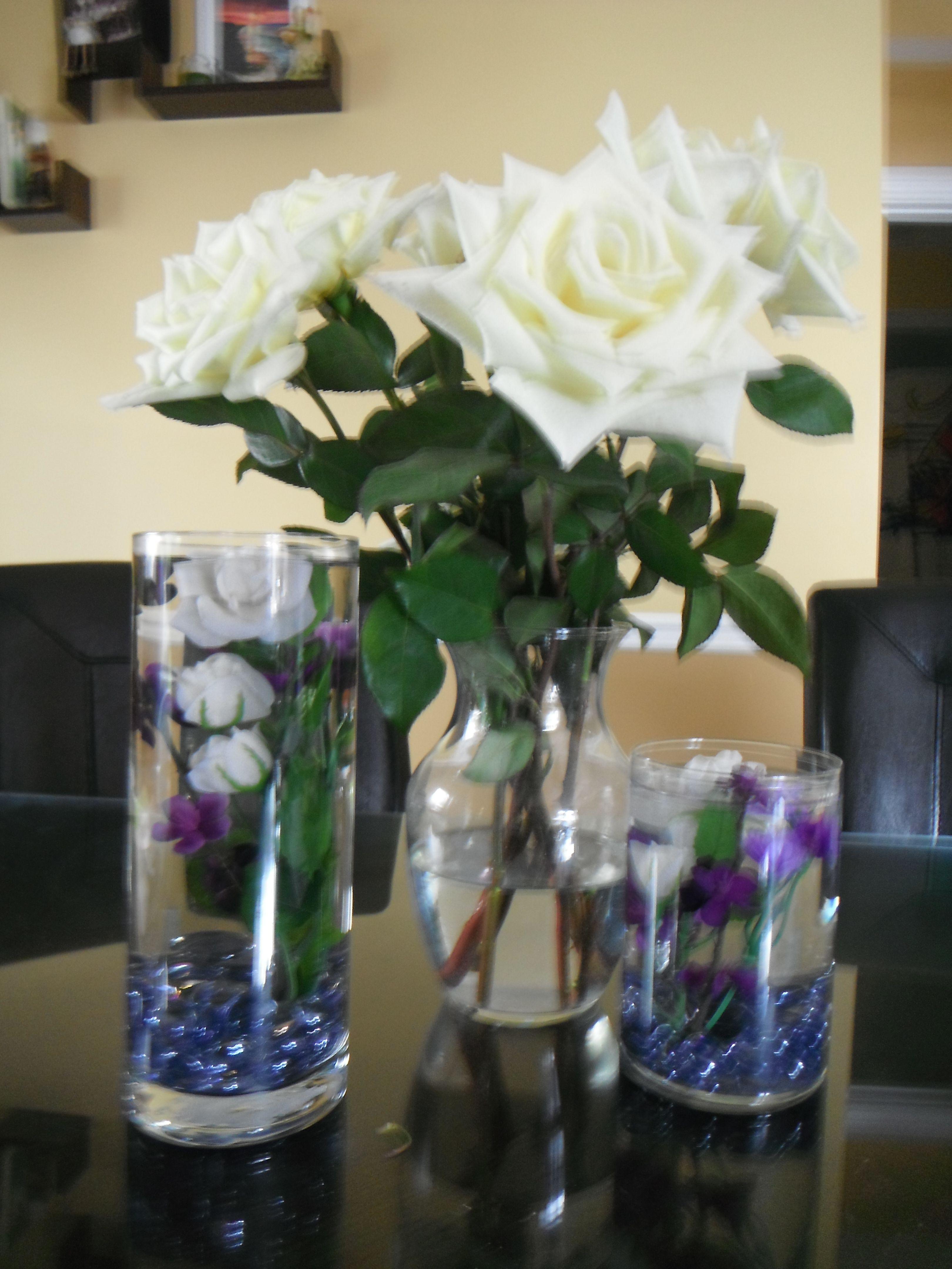 """De vraies roses blanches entourées de mes créations roses blanches et fleurs violettes """"ancrées"""" dans des vases achetés à des prix modiques! Real roses surrounded by my creations: mini white roses and purple flowers """"anchored"""" in water makes for a chic inexpensive centerpiece!"""