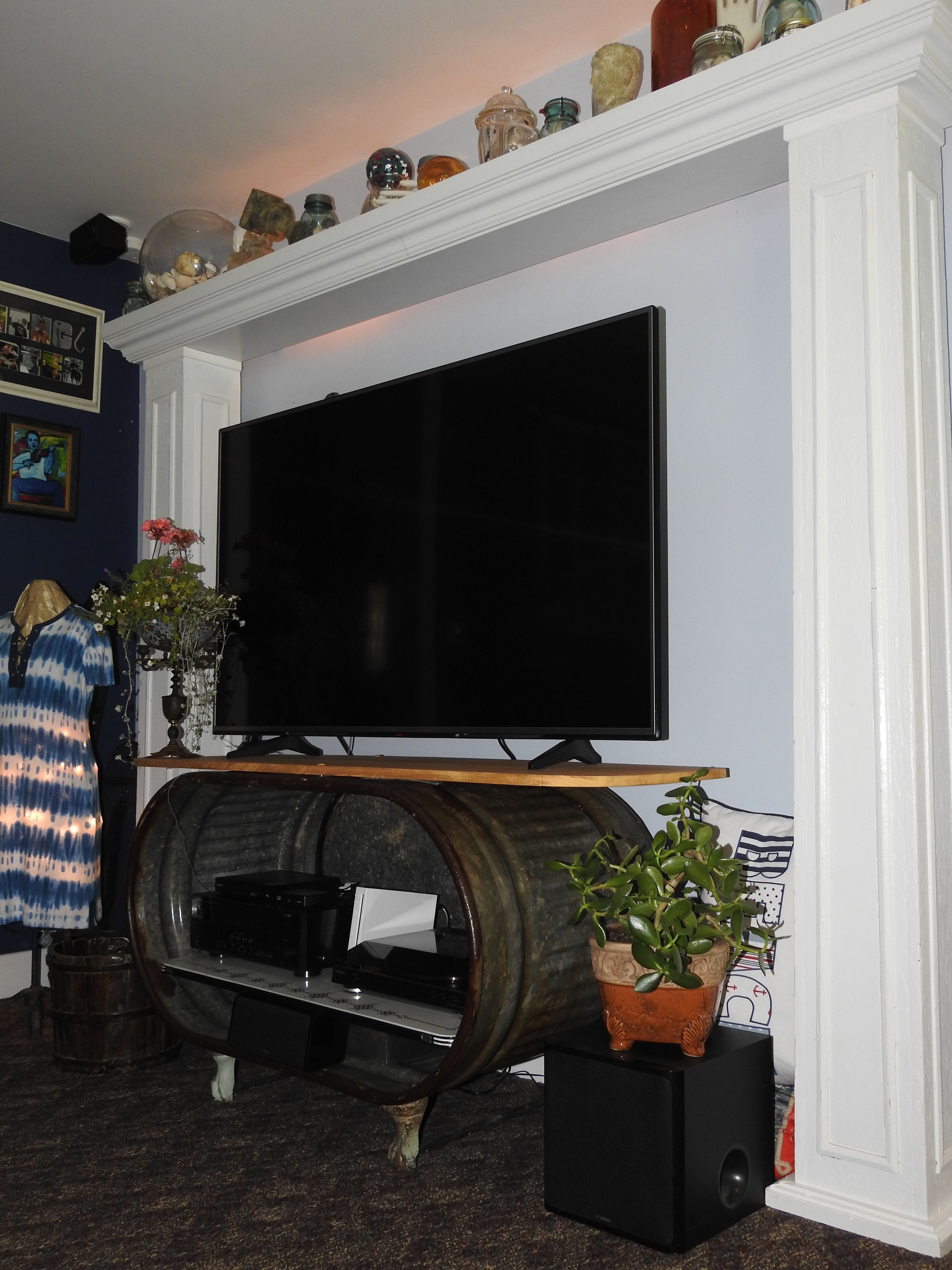 Porch columns topped with fireplace mantle. TV stand made