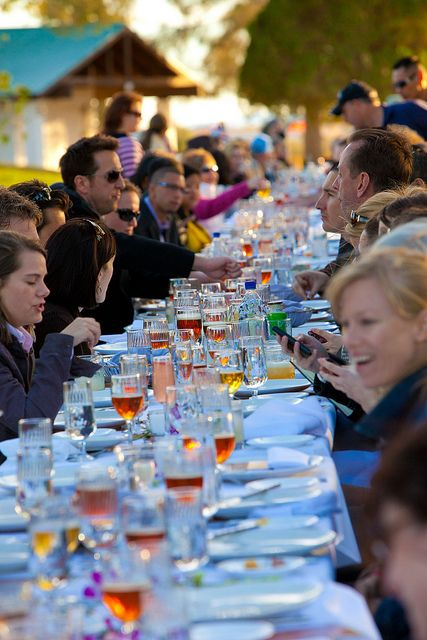 Guests dining and conversating at outdoor party event with rose' and beer