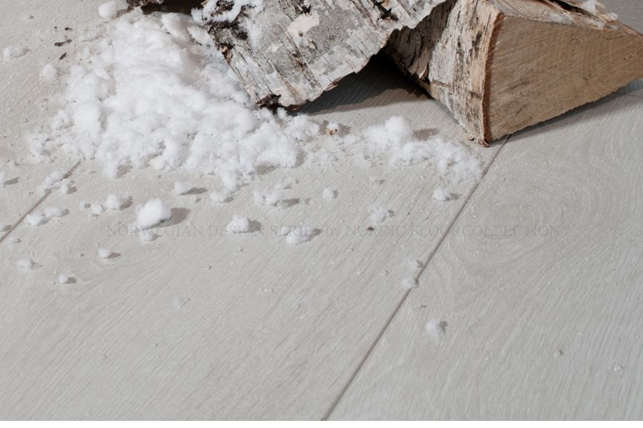 """""""White Winter"""" in inspired by the frozen winter-bridge at the old farm """"Rinde Fjellgard"""" in Telemark, Norway. The color is both pure and elegant. The surface is visually similar to real wood in white tones. Each of the planks has bevelled edges (V Grooves) on all four sides resulting in very distinctive groove between the planks, adding more depth and dimension along with giving an individual definition to each plank."""