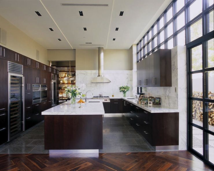 Sleek Kitchen With Espresso Veneer Kitchen Cabinetry Paired With Calcutta Marble  Countertops.