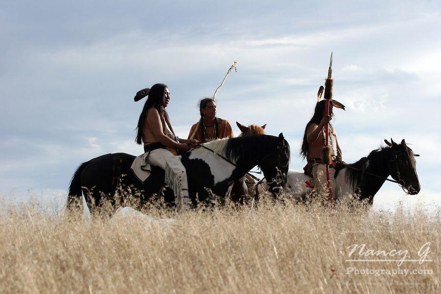 Three Native American Indians on horseback on the prairie of South Dakota