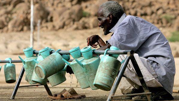 Homem sudanês usa um balde de água para lavar as mãos em campo de refugiados no Estado de Kassala, no leste do Sudão
