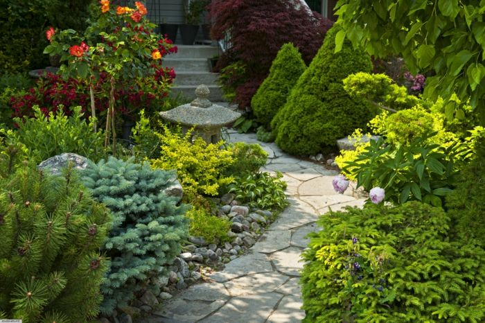 eine japanische Garten Skulptur ein Pfad und viele Pflanzen ...