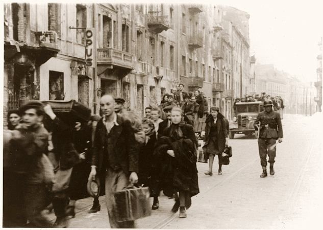 Jews captured by the SS during the suppression of the Warsaw ghetto uprising march to the Umschlagplatz for deportation to Treblinka.