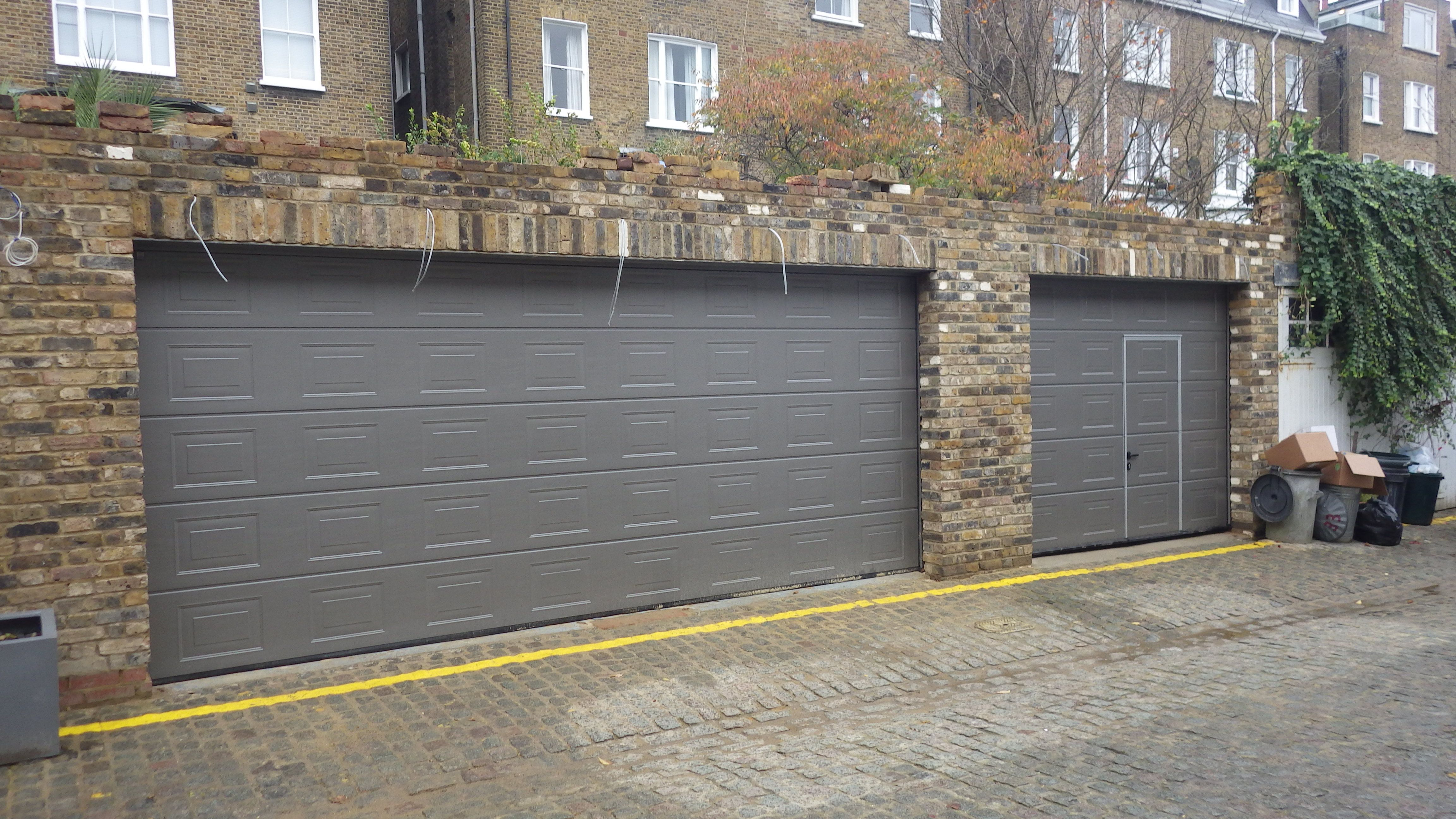 Hrmann sectional s panelled grey aluminium ral 9007 lpu40 doors hrmann sectional s panelled grey aluminium ral 9007 doors with a wicket door built into the smaller of the two garage doors rubansaba