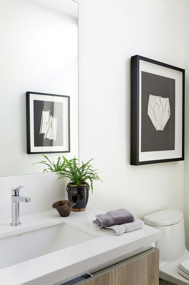 Minimal bathroom with eclectic art and a wooden vanity sink