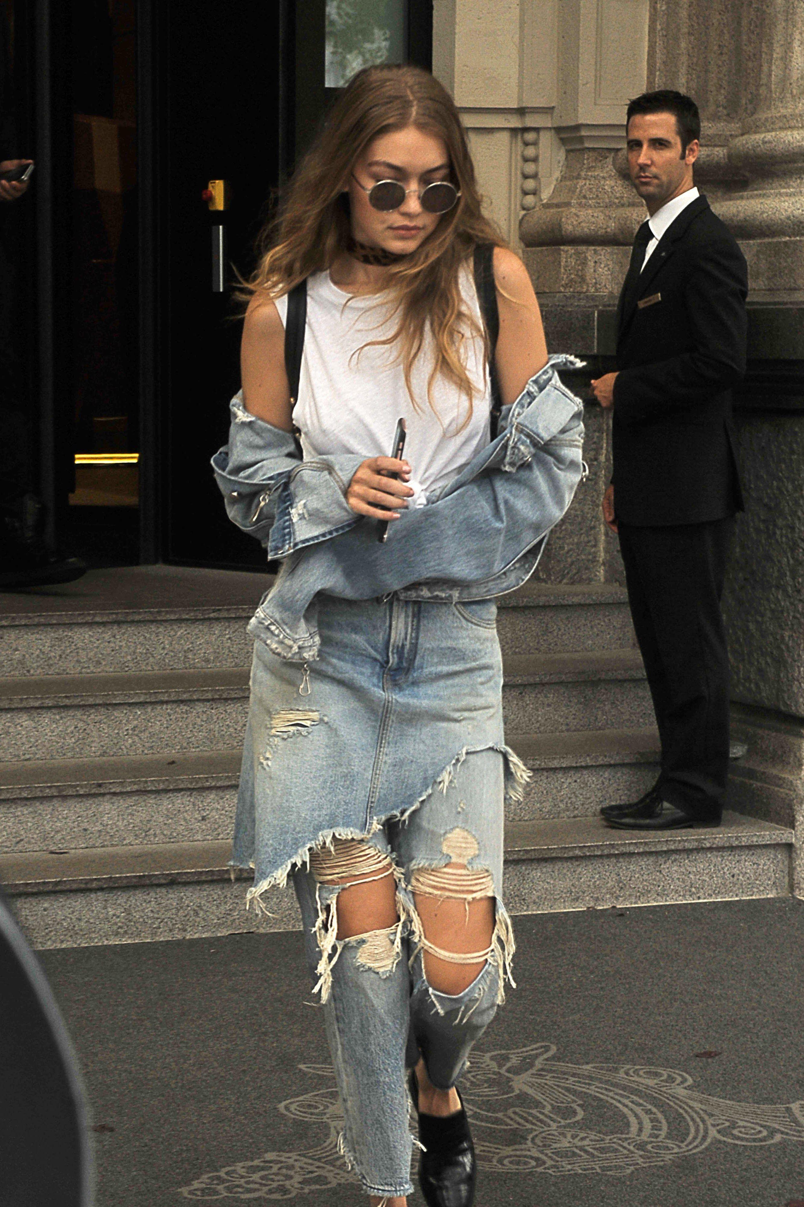 dbdee4cd72 Gigi Hadid Layers Denim Skirt Over Jeans at Milan Fashion Week