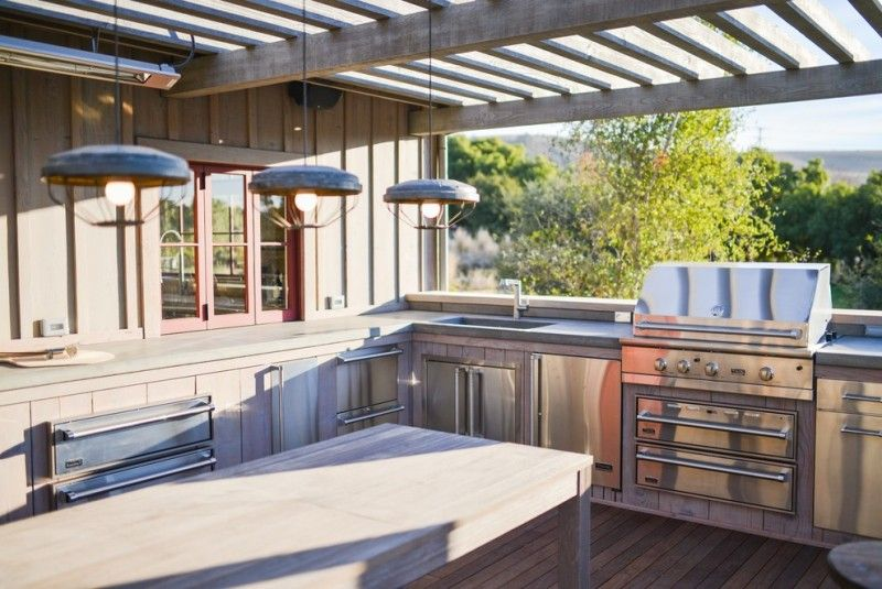 viking outdoor kitchen high end faucets wooden floor long table stainless steel appliances stove oven cabinets drawers hanging lamps window glass ceiling farmhouse style of