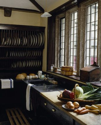 The scullery at Lanhydrock, view of the slate lined sink, draining board and wooden plate rack with fresh vegetables in foreground #plateracks