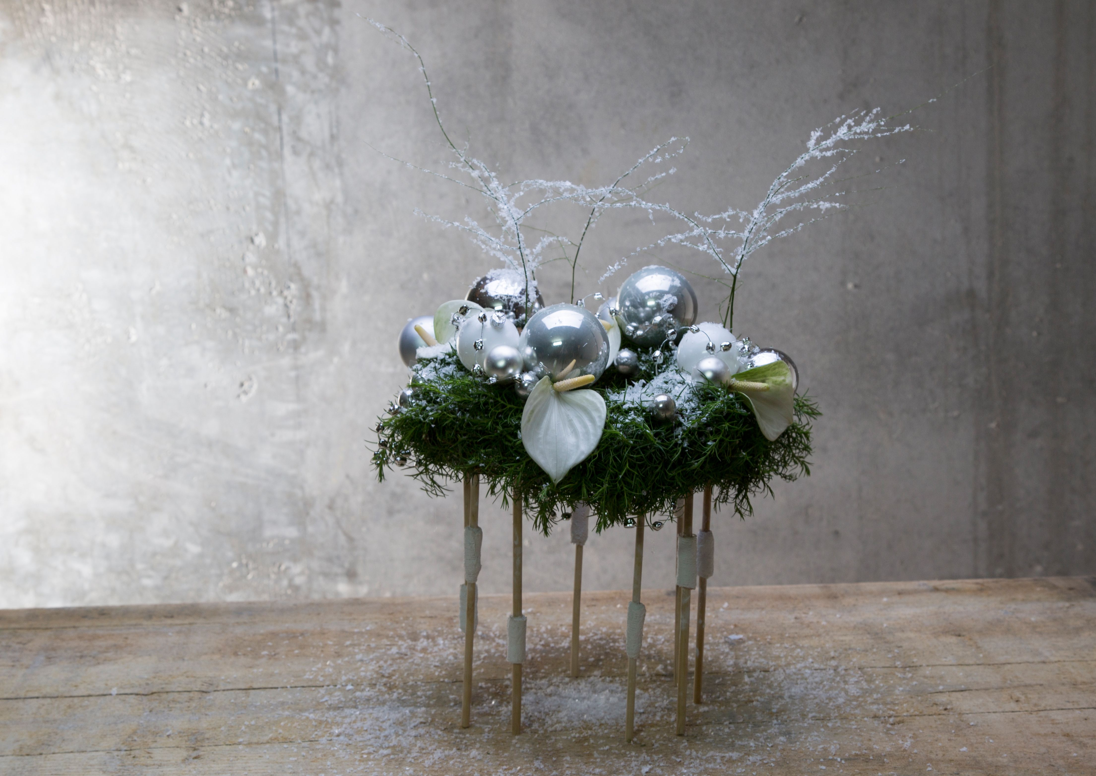 Nelleke Bontje created a silver and white Christmas arrangement with lovely white Anthuriums. Easy but different due to the legs the piece is resting on.