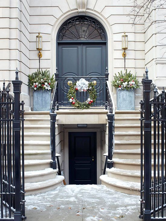 Balance Your Christmas Door Decorations- Ornate doors and wide front entryways need little decoration. Instead, add accents to the surrounding areas to create the perfect holiday look. Two containers flank this wide entry; their placement plays off the elegant front porch's symmetry. Bright silver and red holiday ornaments accent both the containers and the evergreen wreath. (I love this entry!)