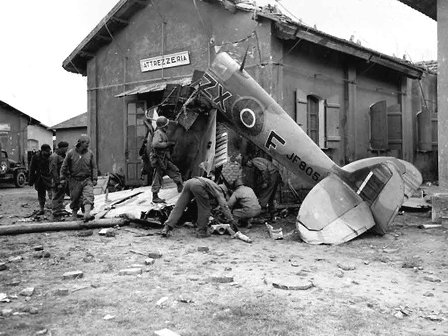 "American soldiers examine the wreckage of a British Spitfire which crashed near Anzio in Italy. The ""Attrezzeria"" building, which is a tool shop, may be the building onto which the plane crashed (January 30, 1944)."