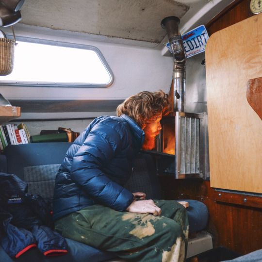 Tucker Gorman firing up the wood stove in his 28 foot sailboat he calls home. / forest huntington