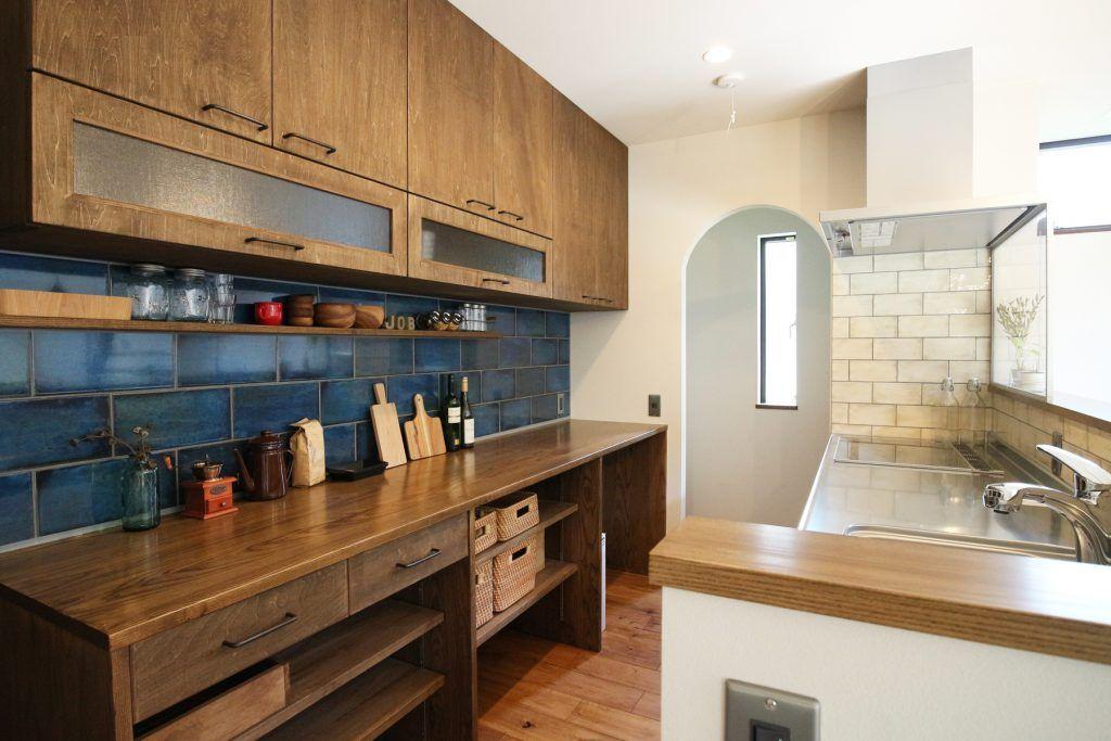 パントリーもあって収納量抜群のキッチン ブルーの大判タイルが空間のアクセントに リビング キッチン キッチン 棚 おしゃれ キッチンフロア
