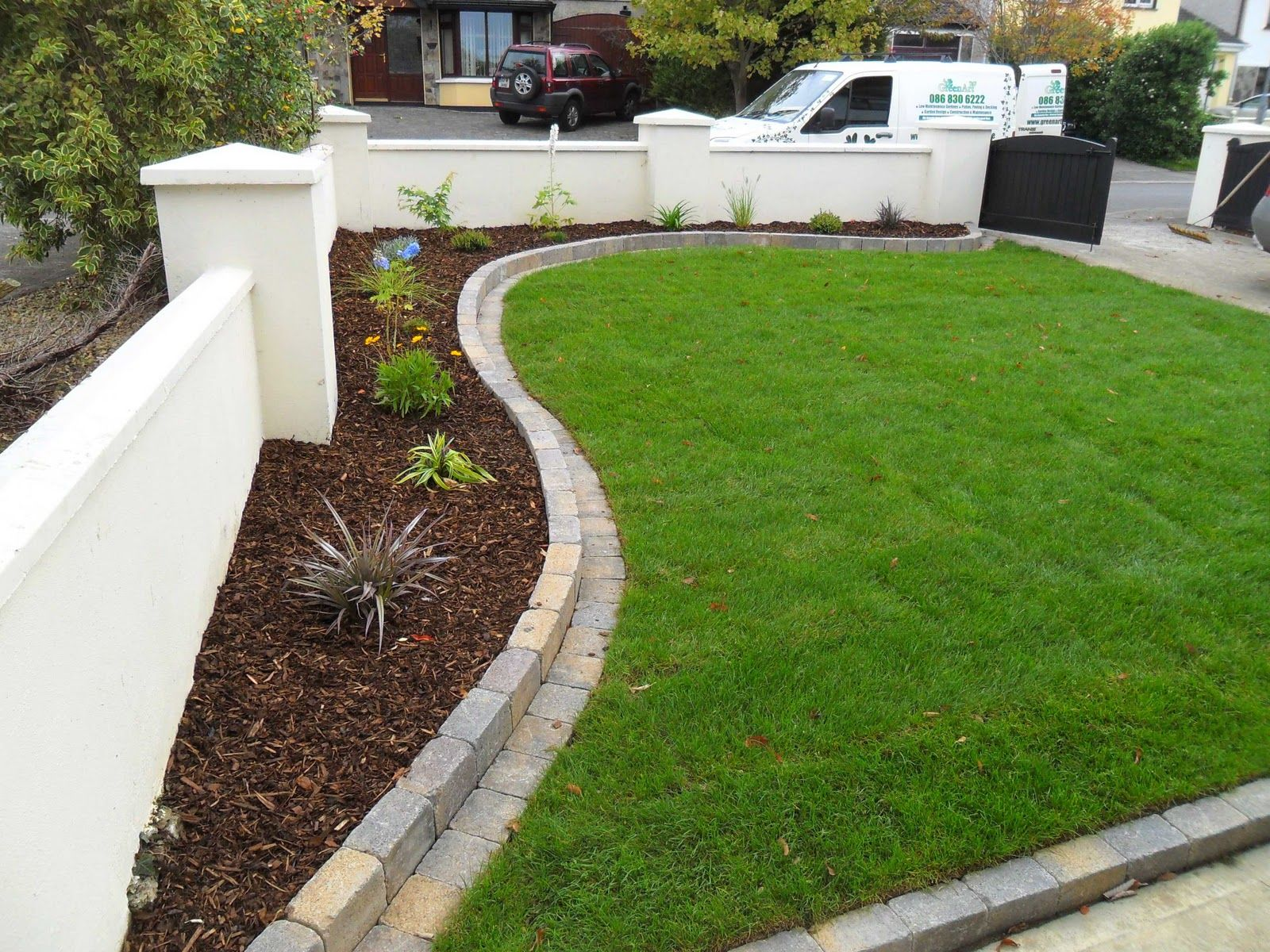 Curving raised bed with mowing edge garden yards for Brick edging for your flower beds