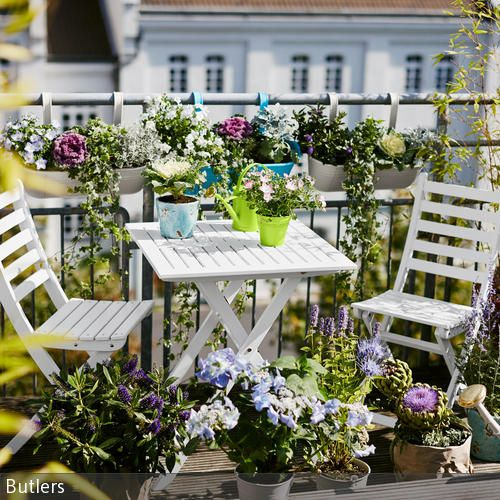 Die weiße Gartenmöbel-Sitzgruppe verleiht diesem Balkon eine klassische Note. Kleine Farbakzente setzen die vielen Blumen und die farbigen Gießkannen. …