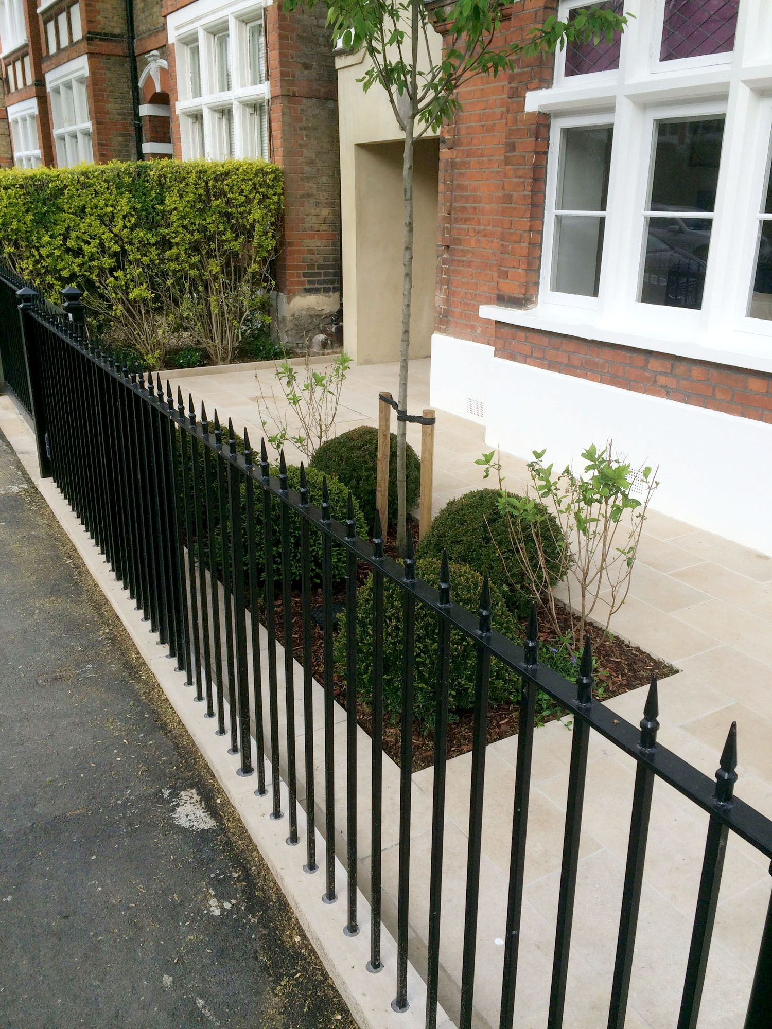 Black cast iron railings and stone paving in contemporary London