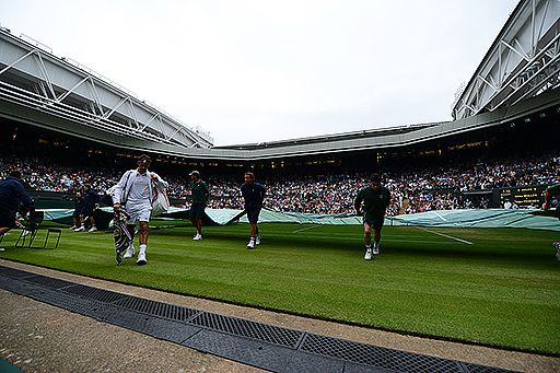Roger Federer walks off Centre Court following a rain delay