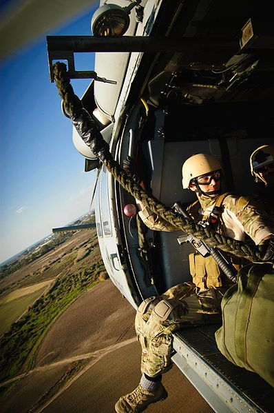 : A U.S. Navy sailor rides in an MH-60 Seahawk helicopter from Helicopter Sea Combat Squadron 28 during rope suspension training with Explosive Ordnance Disposal Mobile Unit 8 and EOD Training and Evaluation Unit 2 in Rota, Spain, on Jan. 11, 2012.
