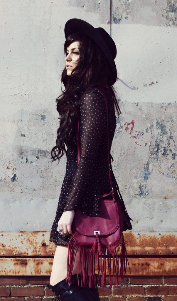 White polka dotted black long sleeved dress, black hat, a choker, and a maroon tasseled handbag, side view