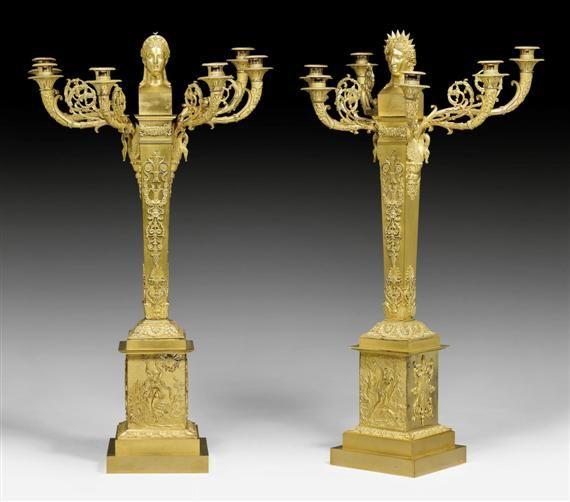 """PAAR PRUNK-GIRANDOLEN """"APOLLON ET DIANE"""", Empire, aus einer Pariser Meisterwerkstatt, wohl gefertigt für den russischen Markt, um 1810/1810. Matt- und glanzvergoldete Bronze. Reich beschmückter Vierkantschaft mit Abschluss in Form einer Apollo- (als Symbol für Sonne und Tag) bzw. Diana-(als Symbol für Mond und Nacht)-Büste und 6 geschweiften, teils eingerollten Lichtarmen mit zylindrischen Tüllen und runden Tropftellern, auf gestuftem Rechteck-Postament."""