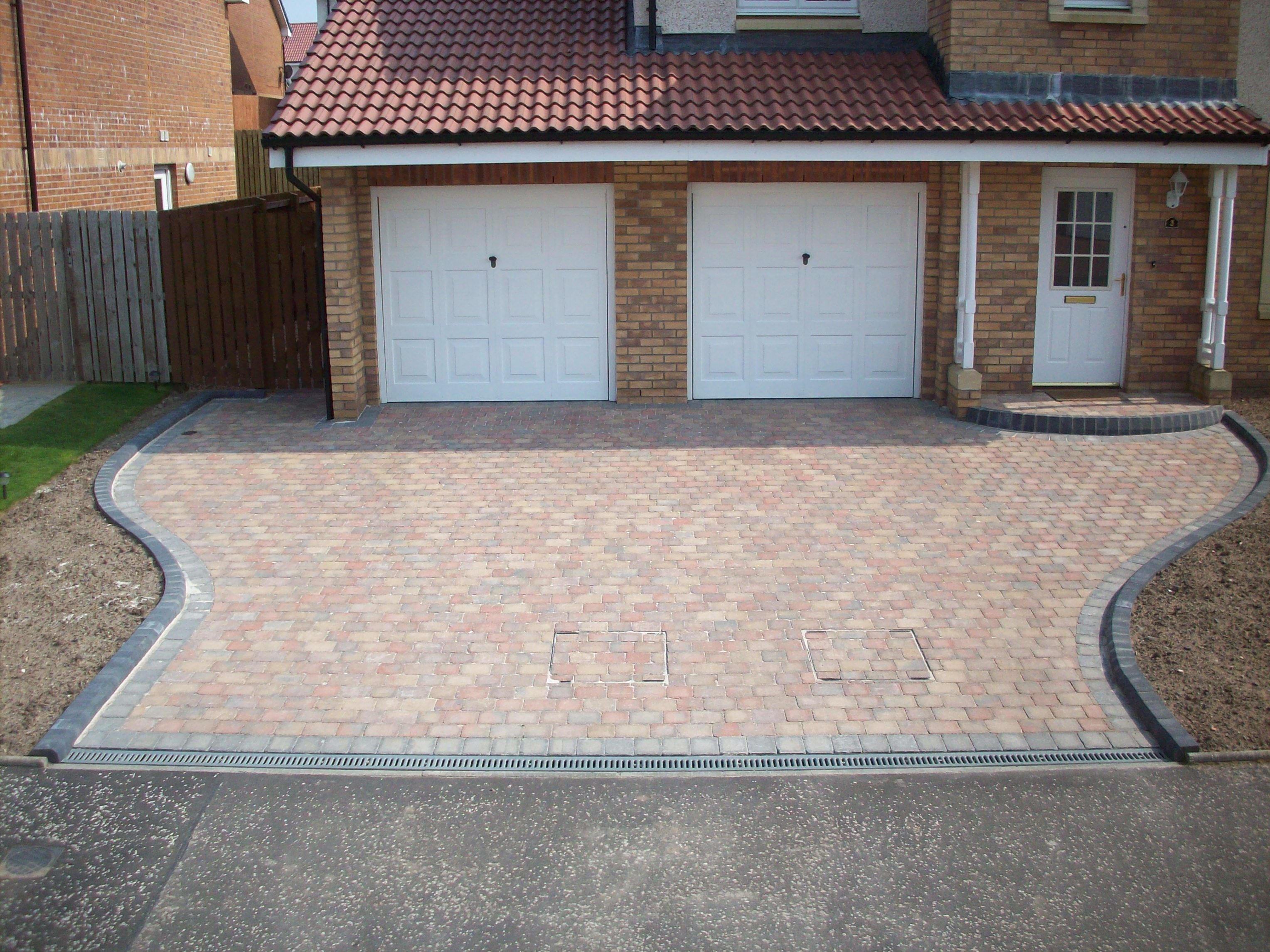 Tegular paving driveway with two manhole inserts, and a ...