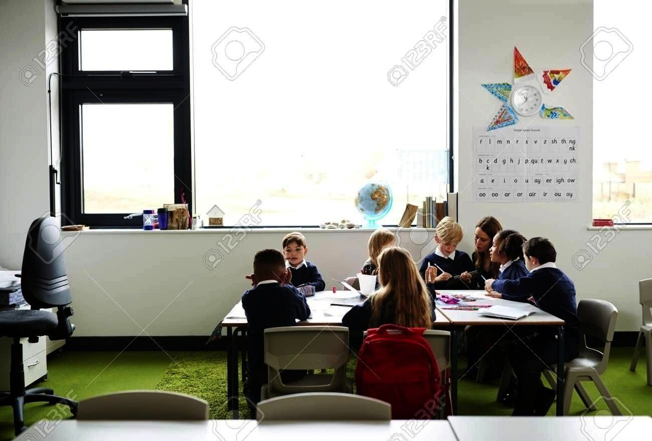 primary school kids sitting at table in a classroom, teacher kneeling to help them during the lesso