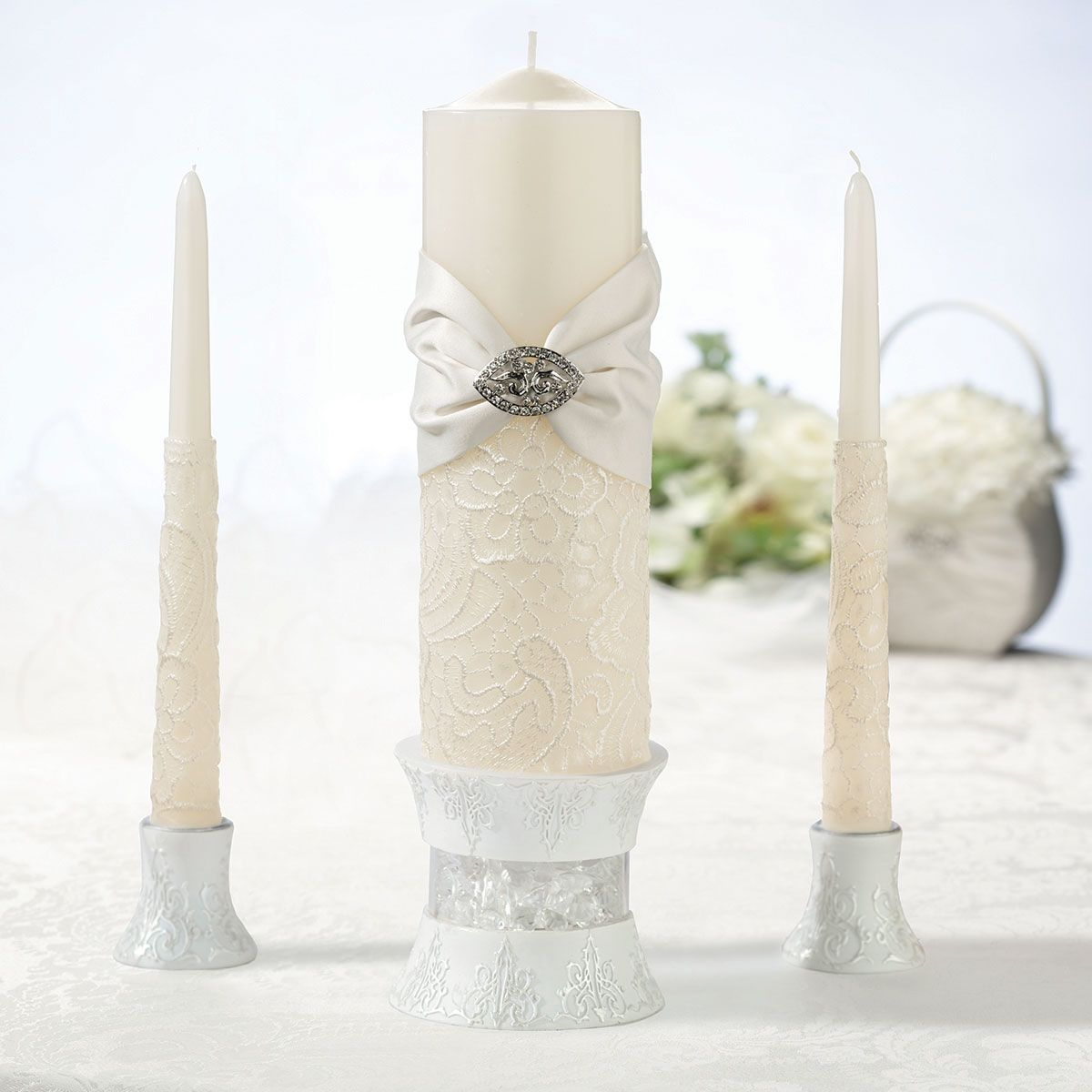 """Lillian Rose Vintage Cream Lace Pillar and Two Tapers This wedding candle set includes two taper candles (9.25"""" tall) and one pillar candle (9"""" tall). Both are made of cream-colored wax and decorated with silver wax in the design of a lace pattern. The pillar candle is wrapped in a cream satin sash accented by a rhinestone ornament. Price $45.00"""