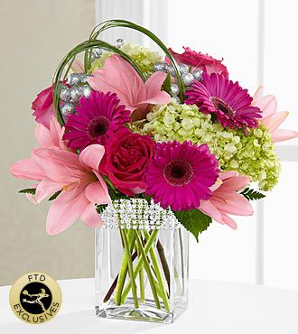 This gorgeous bouquet showcases blushing blooms and definitive style...a gift blossoming with heartfelt happiness. Hot pink roses and gerbera daisies are a standout in this bouquet surrounded by pale pink Asiatic Lilies and the alluring texture of green mini hydrangea blooms perfectly accented with bear grass blades and lush greens to create a simply stunning flower arrangement. Presented in a clear glass vase with silver beading lined at the top, this beautiful arrangement is sure to be a…