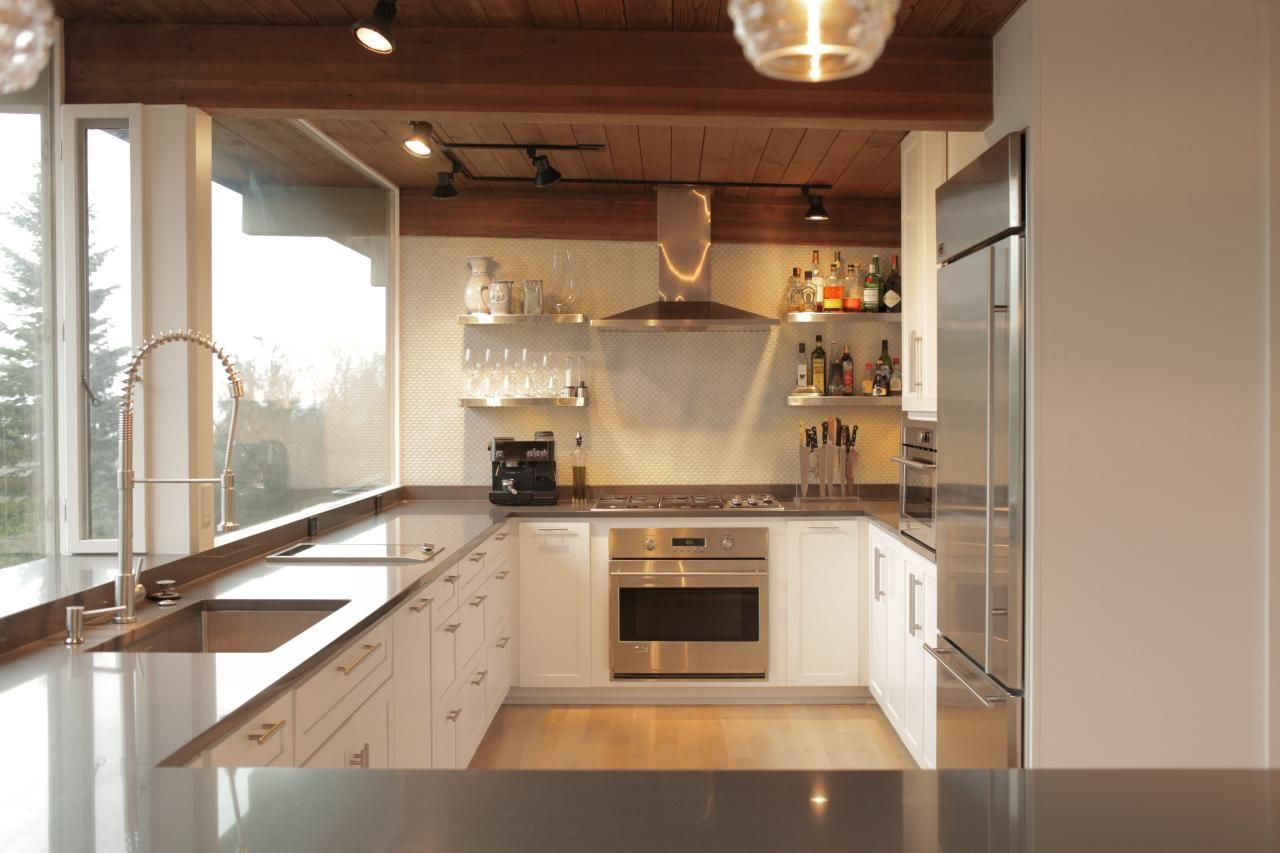 sleek gray countertops look clean and crisp against the white cabinets and backsplash in this midcentury
