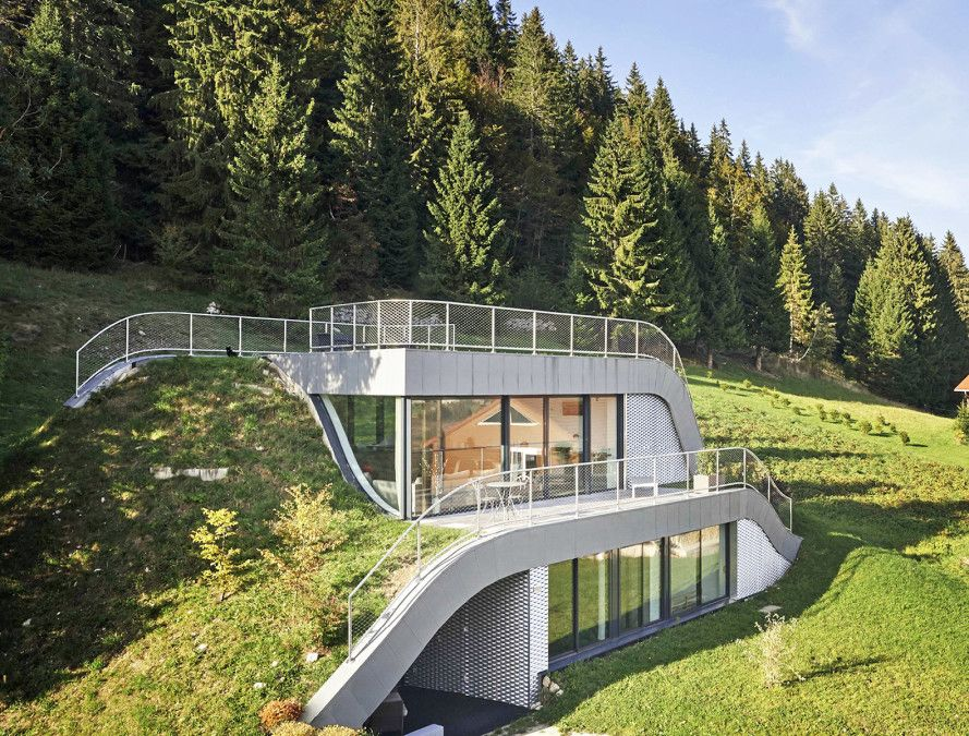 Wavy green roofed casa jura disappears into france s for House plans on hill slopes