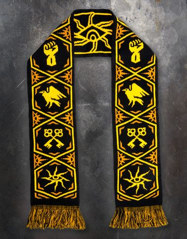 An image of the Inquisition Scarf. It is a thick black scarf with symbols of the Inquisition, Force, Secrecy, and Diplomacy in yellow and marigold. The fringe on the ends is black, yellow, and marigold.