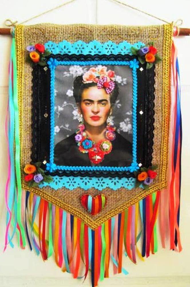 ***MODELO EXCLUSIVO ARTE E OFÍCIO ATELIÊ*** <br> <br>Confeccionado em juta, detalhes bordados, bem colorido, imagem em lona de Frida Kahlo. <br>Med. aprox: Só a bandeira mede 36 x 27 cm e no total com cordão e franjas 55 x 34 cm