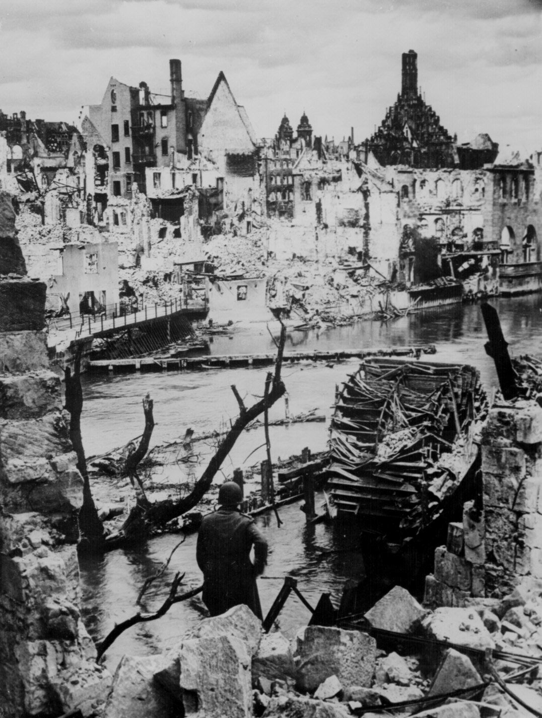 A US Army soldier observing the damage done to an industrial town near Nuremberg, April 1945