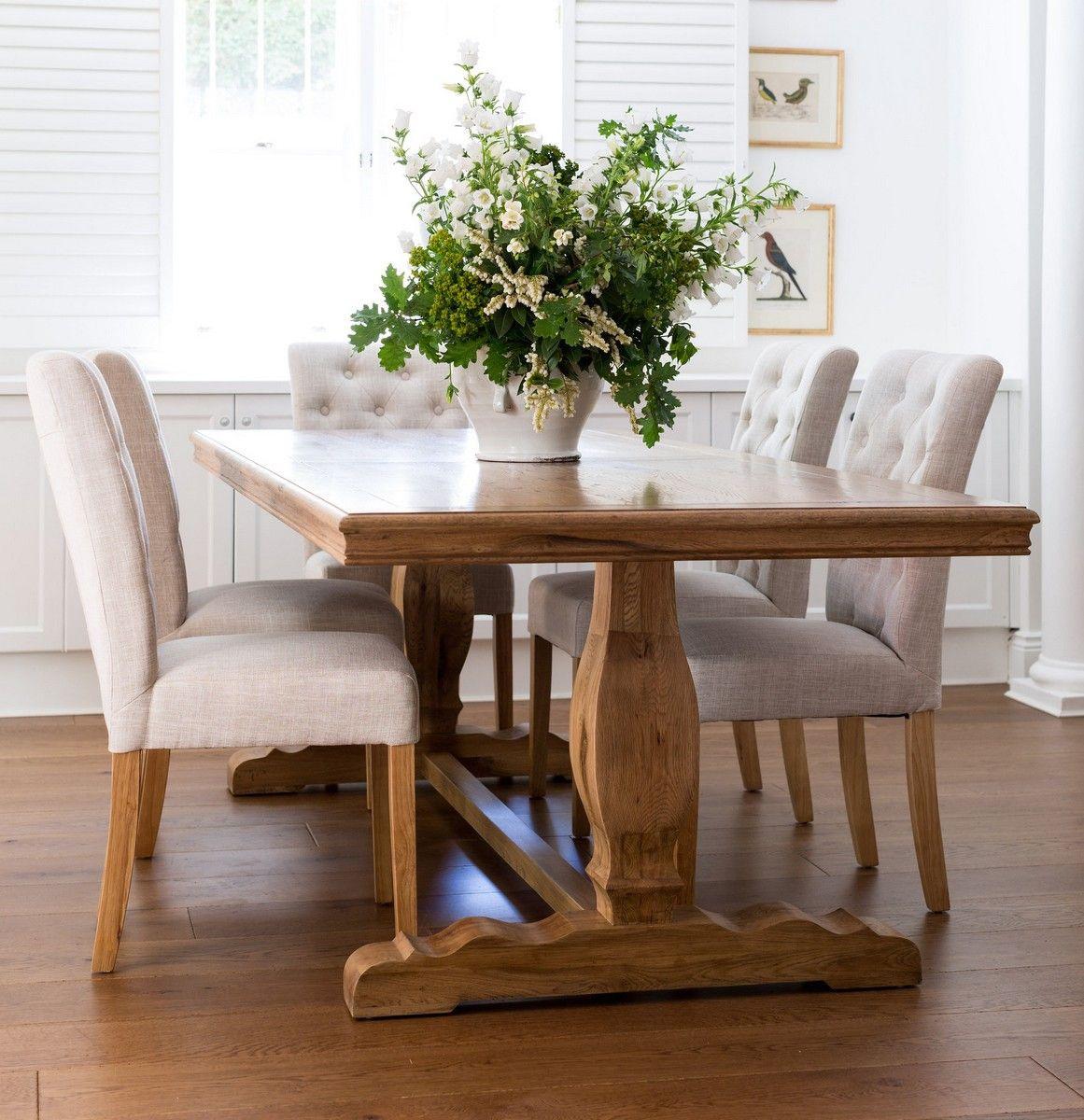 comfortable white padded chairs and wide farmhouse style dining table in traditional dining area. Black Bedroom Furniture Sets. Home Design Ideas