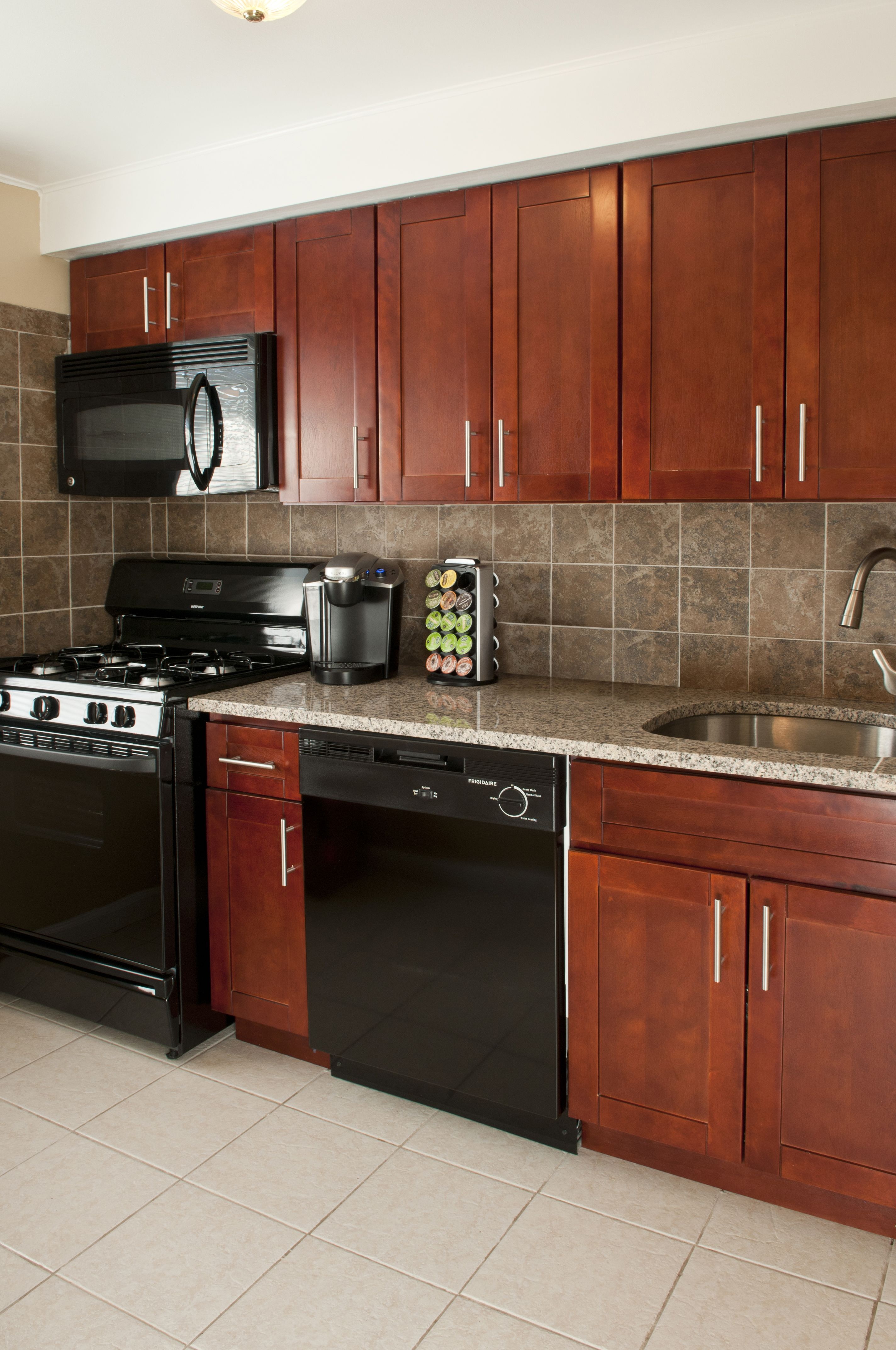 Cherry Cabinets, Granite Countertops, Black Appliances, Including  Dishwashers And Built In Microwaves,