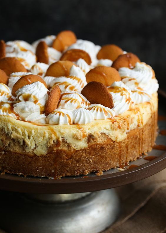 Banana Pudding Cheesecake is a combo of my two most favorite classic desserts! Real bananas and vanilla cookies fill the cheesecake, which all sits on a vanilla cookie crust and is topped with fluffy whipped cream, more cookies and caramel! #cookiesandcups #cheesecake #bananapudding #nelliesfreerangeeggs #spon #cheesecake
