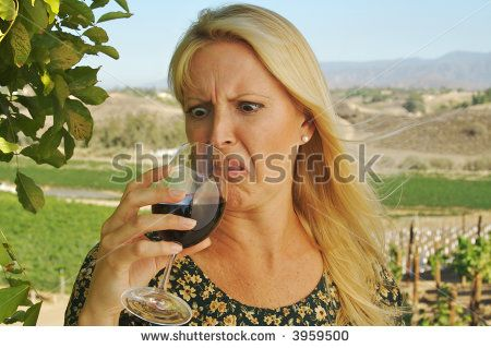Beautiful woman at a country winery wearing her sun dress on a summer day. Apparently the wine is not so good there.