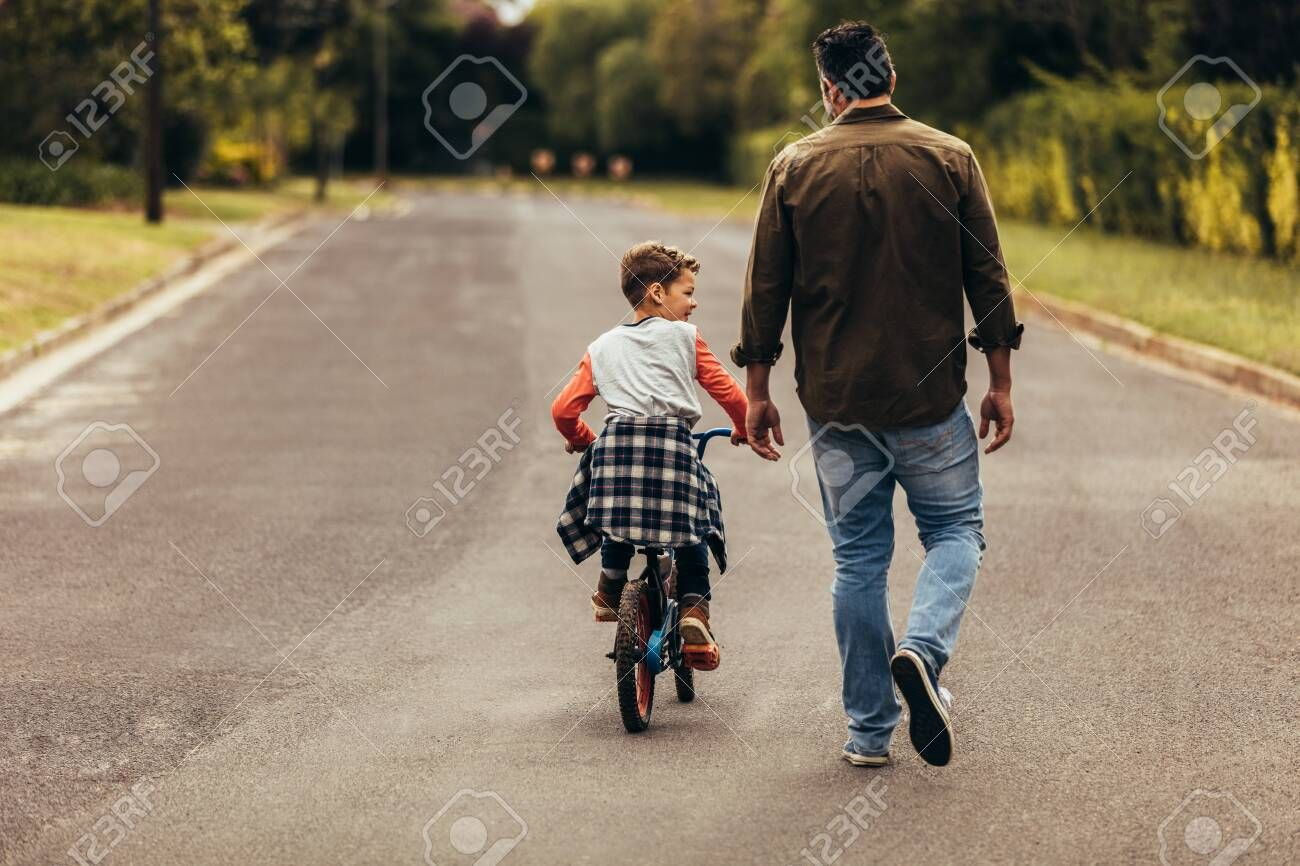 Kid Learning To Ride A Bicycle On An Empty Road Rear View Of A