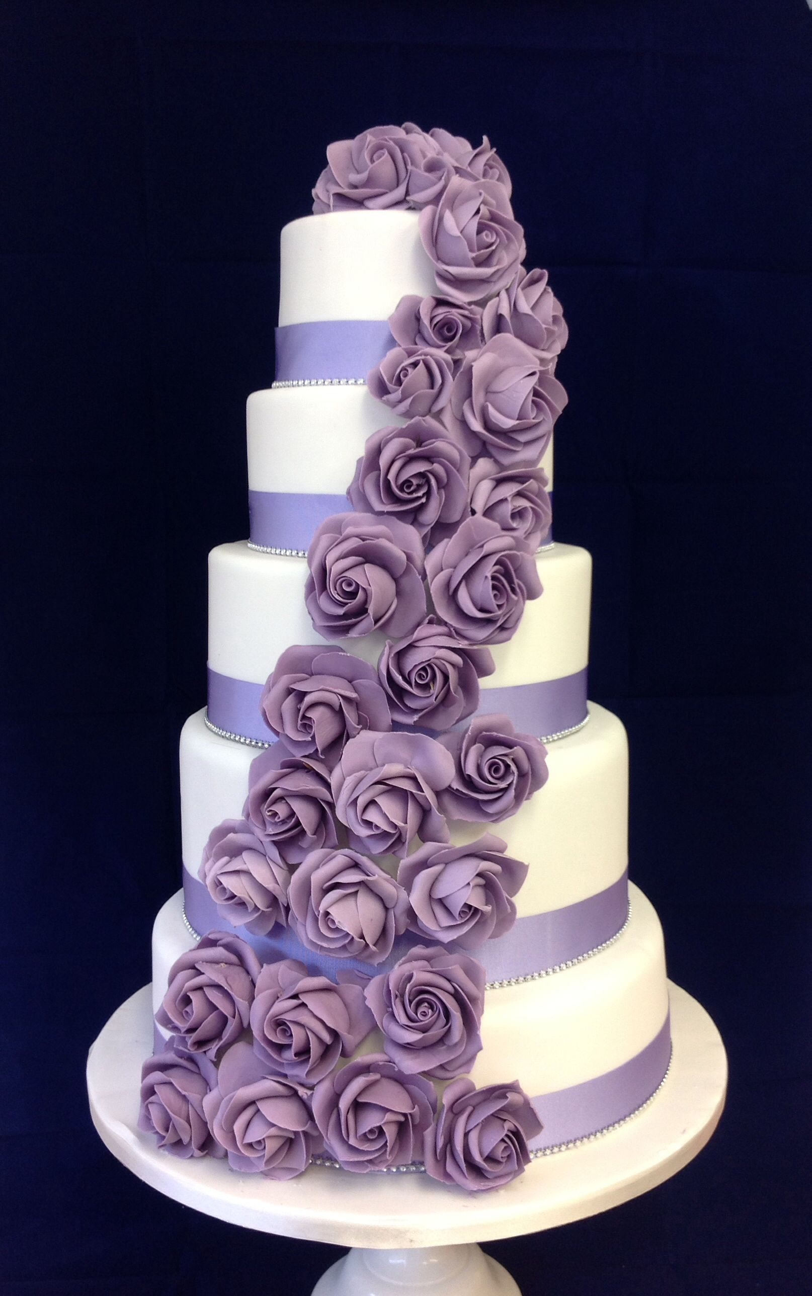 stunning 5 tier wedding cake with purple rose cascade. wedding