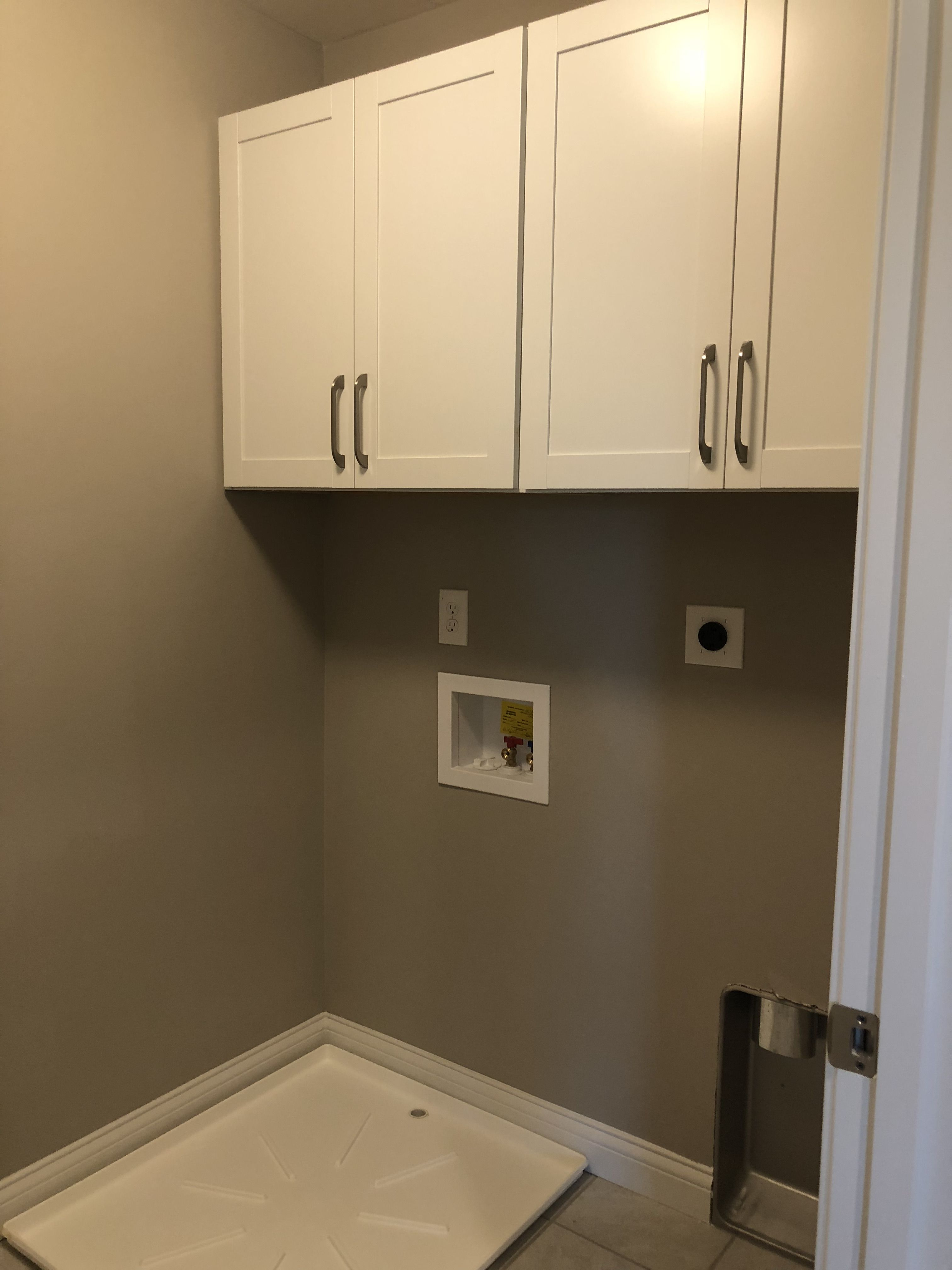 Brellin White Cabinets Above Washer Dryer In Laundry Room
