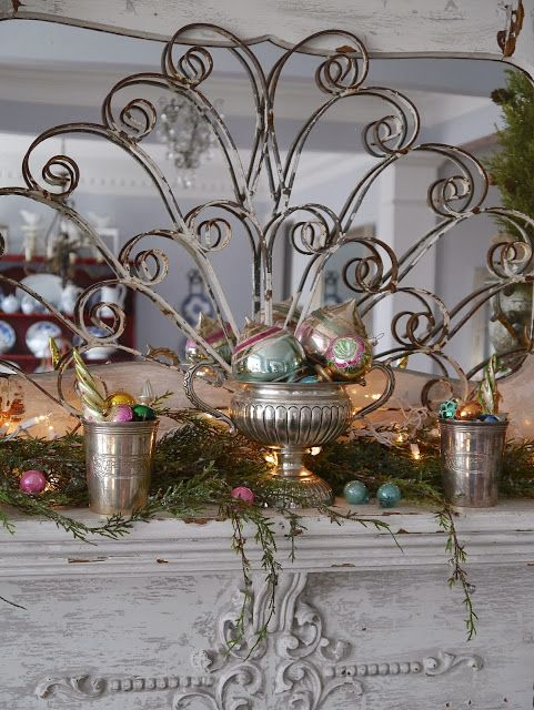 .lovely scrolled iron behind pretty ornaments in  silver....interesting...