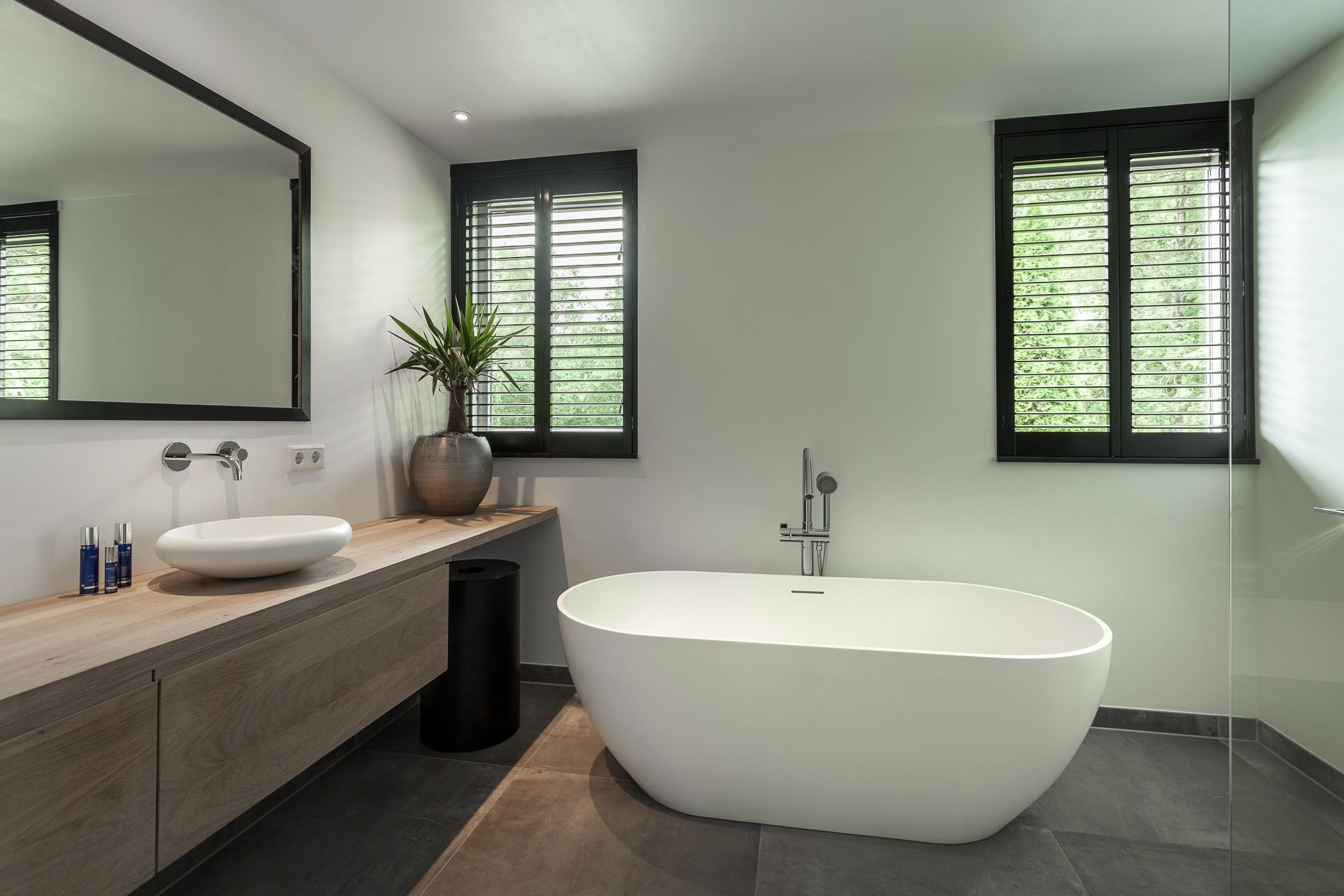 Zwarte shutters in moderne badkamer solid surface bad en