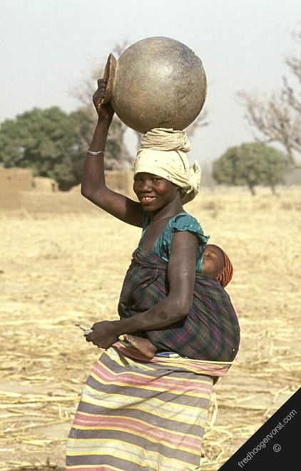 woman carrying bundles on back | faso sahel country smiling