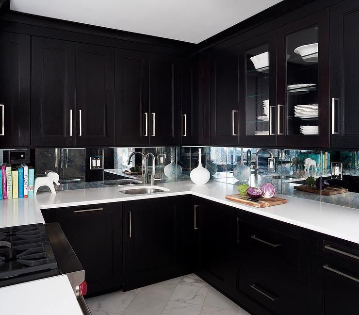 Contemporary Kitchen Features Espresso Cabinets Paired With White Quartz  Countertops And A Mirrored Backsplash.