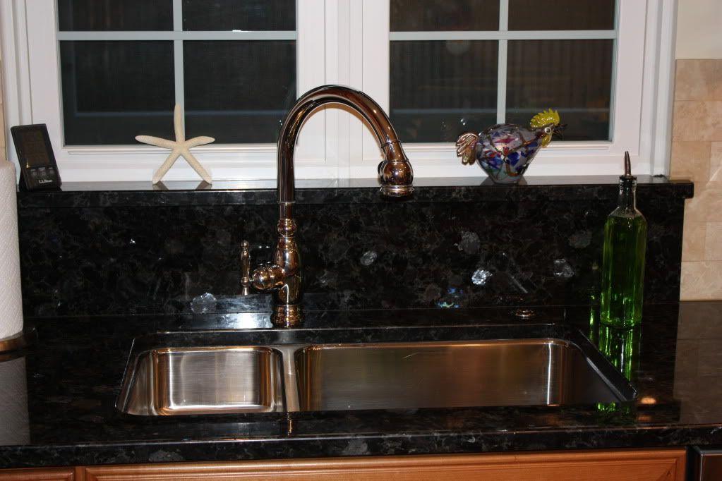 Up Close Of A Sink To Window Granite Backsplash