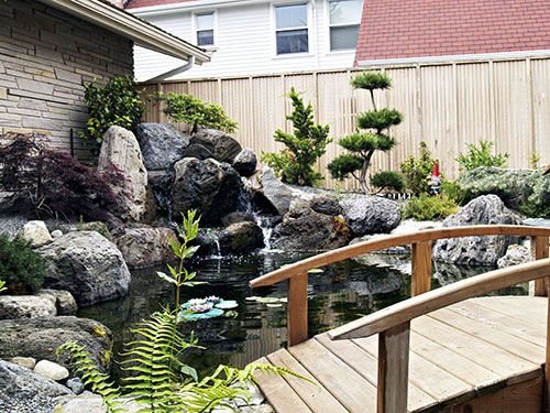 Japanese water garden koi pond site has more pics of the for Koi pond design with bridge