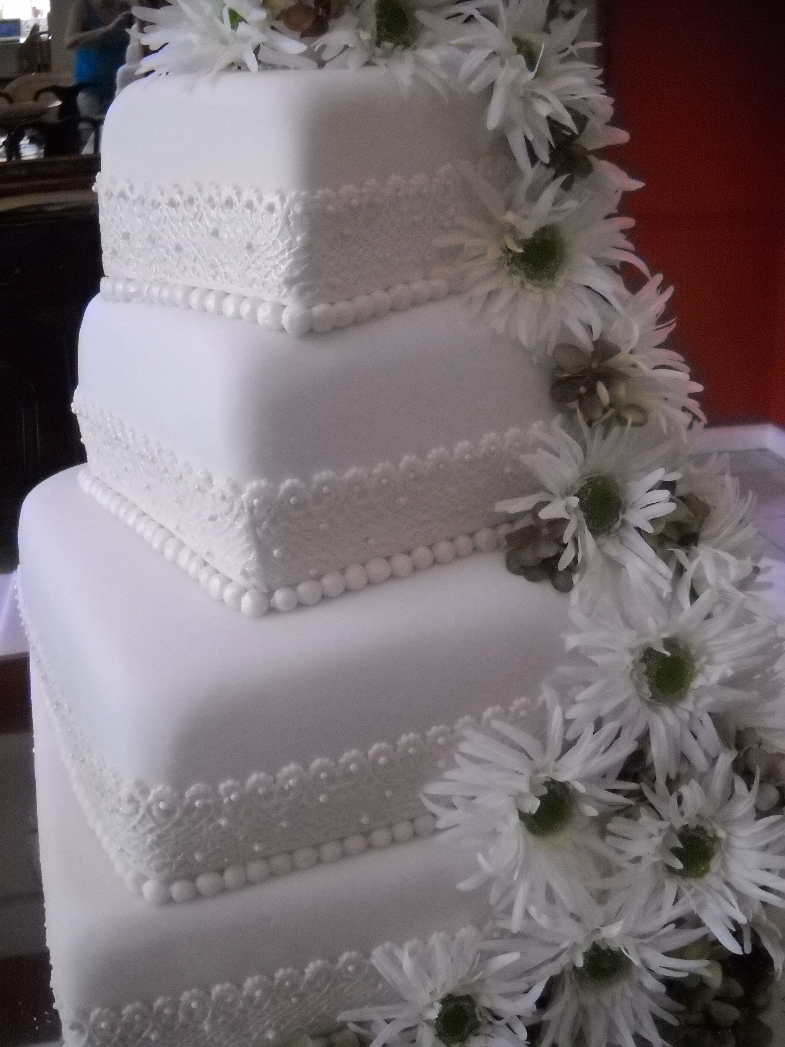 - Slightly twisted on each other, this square design was embellished with a 'lace ribbon' and silk gerberas....